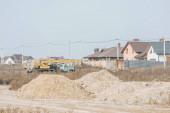 Pískové formy na polní cestě se stavebním jeřábem a domy na pozadí