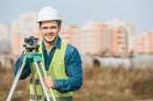 Lächelnder Vermessungsingenieur in Harthut und Warnweste mit digitalem Pegel