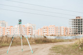 Digitális szint geodéziai méréshez földúton épületekkel a háttérben