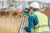 Fotografie Vermessungsingenieur schaut durch digitale Ebene im Feld