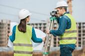 Vermessungsingenieure arbeiten mit Blaupause und digitaler Ebene