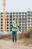 Fotografie Usmívající se zeměměřič drží pravítko s staveništěm na pozadí
