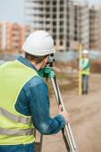 Selektiver Fokus von Vermessungsingenieuren, die Grundstücke mit digitalem Pegel auf der Baustelle messen