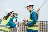 Surveyors using tablet and digital level on construction site