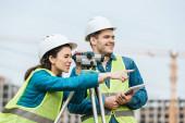 Surveyor se dívá přes digitální úrovni a ukazuje na kolegu s tabletem