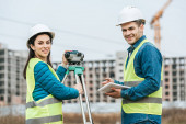Smiling surveyors with digital level and tablet looking at camera