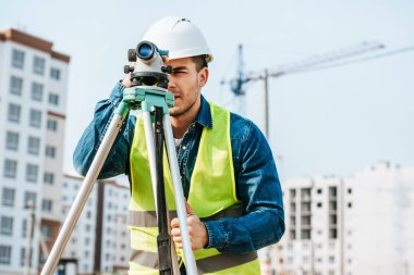 Surveyor looking throughout digital level on construction site
