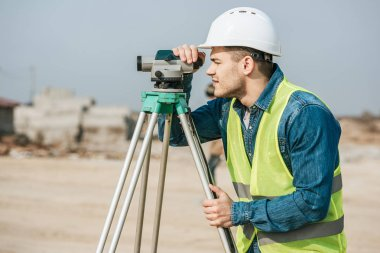 Side view of surveyor in hardhat looking throughout digital level on construction site stock vector