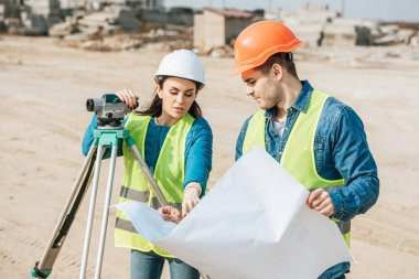 Surveyor with digital level pointing on blueprint to colleague stock vector