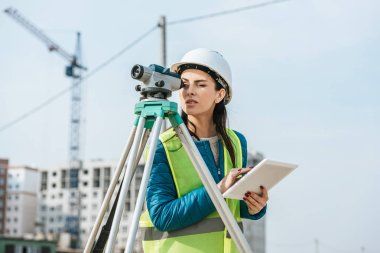 Surveyor with digital tablet looking through measuring level on construction site