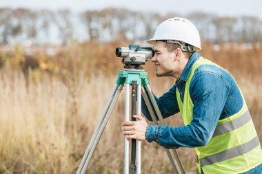 Side view of surveyor looking through digital level in field stock vector