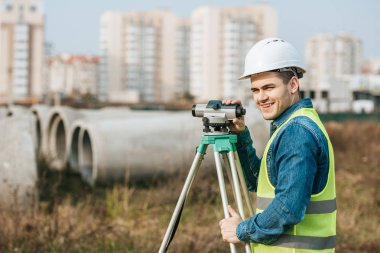 Surveyor with digital level smiling at camera with building materials at background stock vector