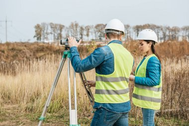 Surveyors working with digital level in field stock vector