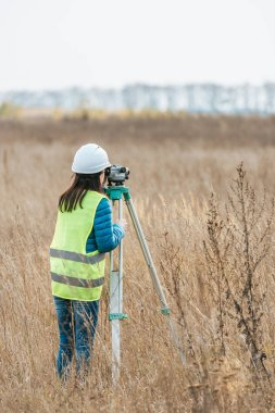 Back view of surveyor working with digital level in field stock vector