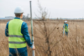Selective focus of surveyors measuring land with digital level and ruler in field