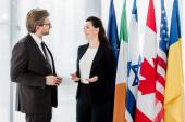 šťastný velvyslanec gestikuluje při rozhovoru s diplomatem v blízkosti vlajek na velvyslanectví