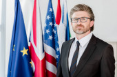 handsome diplomat in glasses looking at camera near flags
