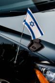 zblízka izraelská vlajka s hvězdou Davida na černém autě