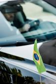 selektivní zaměření brazilské vlajky poblíž člověka v moderním autě
