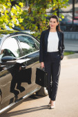 attractive diplomat standing with hand in pocket near car