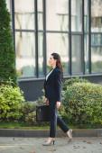 boční pohled na atraktivní diplomatickou procházku s aktovkou v blízkosti budovy