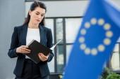 selektivní zaměření atraktivního diplomata při pohledu do složky poblíž vlajky Evropské unie