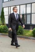 vousatý diplomat v brýlích držící kufřík a kráčející poblíž budovy