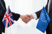 oříznutý pohled na velvyslance, jak si potřásají rukama poblíž Evropské unie a vlajek sjednoceného království