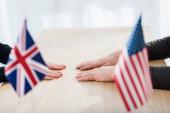 ostříhaný pohled na diplomaty v blízkosti vlajek Ameriky a sjednoceného království