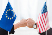 selective focus of diplomats bumping fists near flags of usa and european union