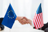 selective focus of flags of usa and european union near diplomats shaking hands