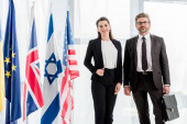 veselí velvyslanci stojící poblíž vlajek různých zemí
