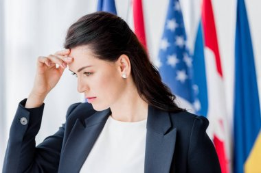 tired and attractive diplomat touching head