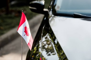 selective focus of canadian flag with maple leaf on black car
