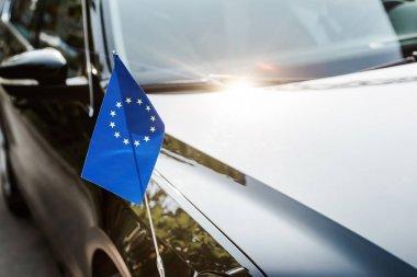 Selective focus of european union flag near black shiny car stock vector