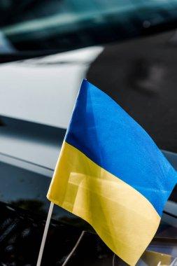 close up on ukrainian flag near black modern car