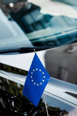 Selective focus of european union flag near black car stock vector