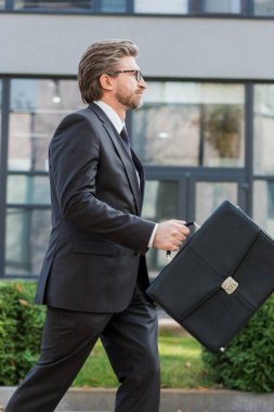 side view of bearded diplomat in glasses holding briefcase and walking near building