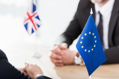 Selective focus of european union flag near ambassadors with clenched hands stock vector