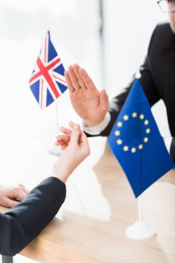 Cropped view of diplomat of european union showing money gesture near ambassador of united kingdom stock vector