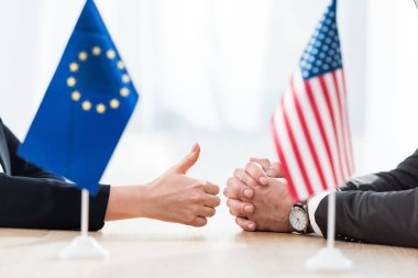 Cropped view of diplomat of european union showing thumb up near ambassador of usa sitting with clenched hands stock vector
