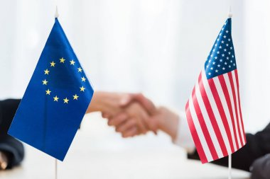 Selective focus of flags of usa and european union near diplomats shaking hands stock vector