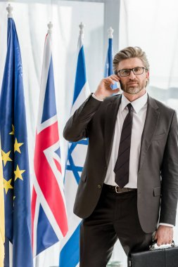 handsome diplomat in glasses talking on smartphone near flags