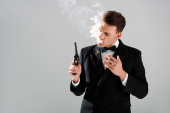 Gefährlicher Mann im Anzug mit Fliege und Pistole beim Zigarrenrauchen