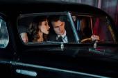 selektivní zaměření muže dotýkajícího se volantu a sedící poblíž atraktivní ženy v retro autě