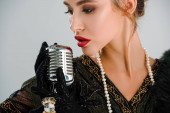 beautiful woman touching vintage microphone isolated on grey