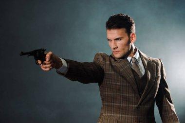 Handsome armed man holding gun on black stock vector