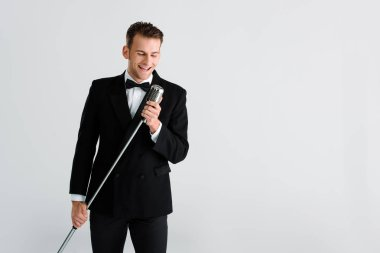 happy singer touching retro microphone isolated on grey