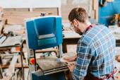 bärtiger Holzarbeiter mit CNC-Maschine in der Werkstatt