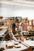 selective focus of bearded woodworker measuring wooden plank